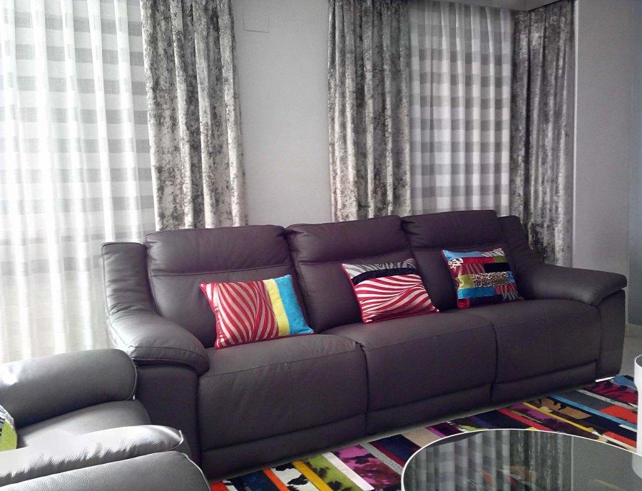 Sofá de piel gris con cojines - Villalba Interiorismo