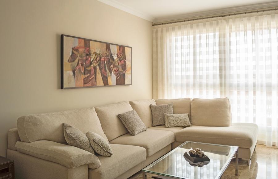 Salón con cortina y sofá en tonos naturales - Villalba Interiorismo