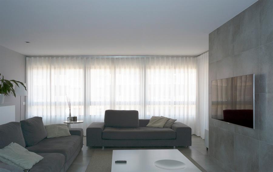 Salón moderno balnco y gris con cortinas colocadas en onda perfecta - Villalba Interiorismo